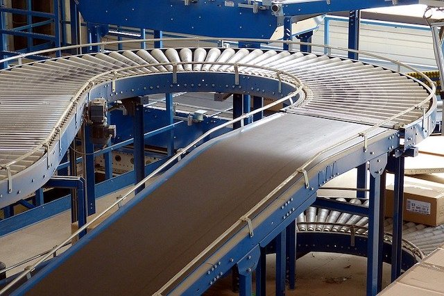 A close up photo of a silver and blue conveyor belt system in an industrial setting.