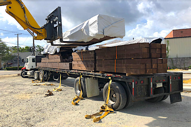 A large flatbed truck is having cargo loaded onto it by a yellow crane. The back end of the truck is facing towards the camera at an angle, and most of the crane is out of the photo, with only the part of the crane holding the cargo showing. The cargo looks like long blocks of wood.