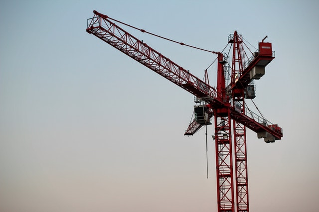Close up of the top of a crane against the sky at twilight.