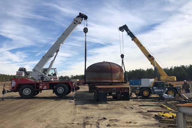 Two cranes lifting heavy metal dome with rigging service from B & B Crane.